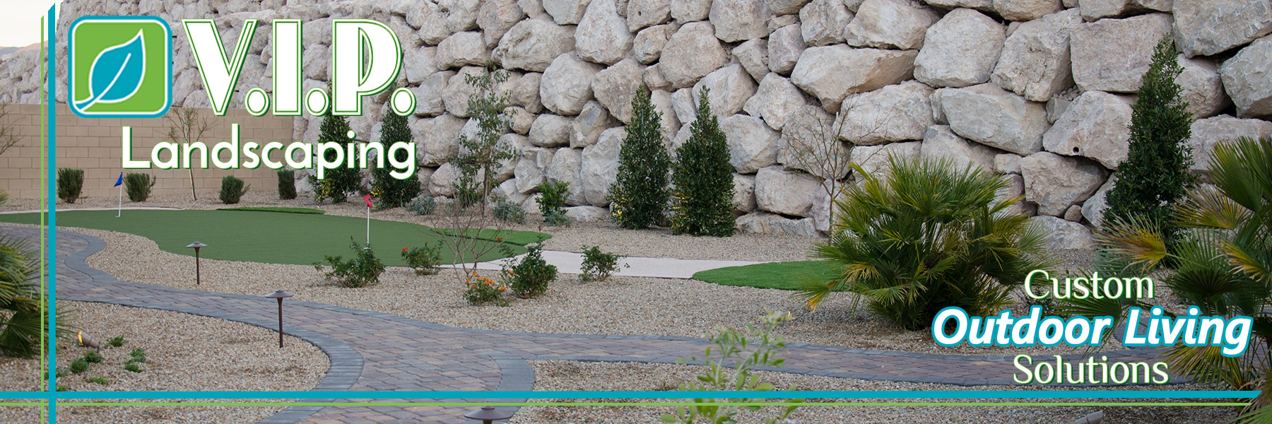 Putting green with boulder rock wall and pavers pathways combined with desert landscaping